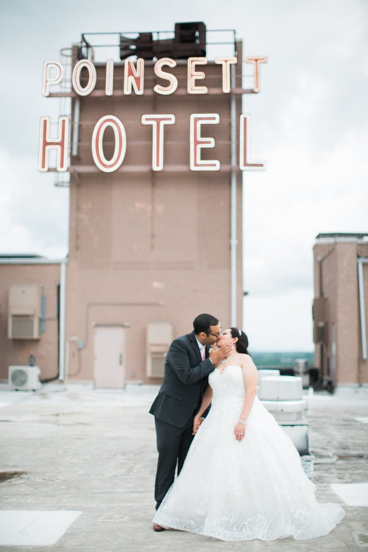 Wedding Photographer, couple kissing beneath a hotel sign