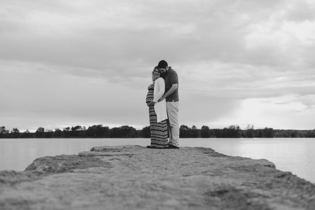 black and white photo of expecting parents at the end of a rock pier