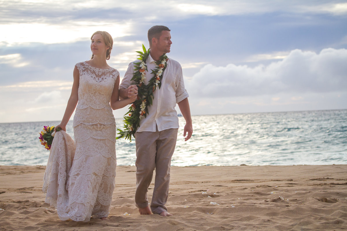 Bride and groom walking in the sand after their Kauai wedding on the beach.