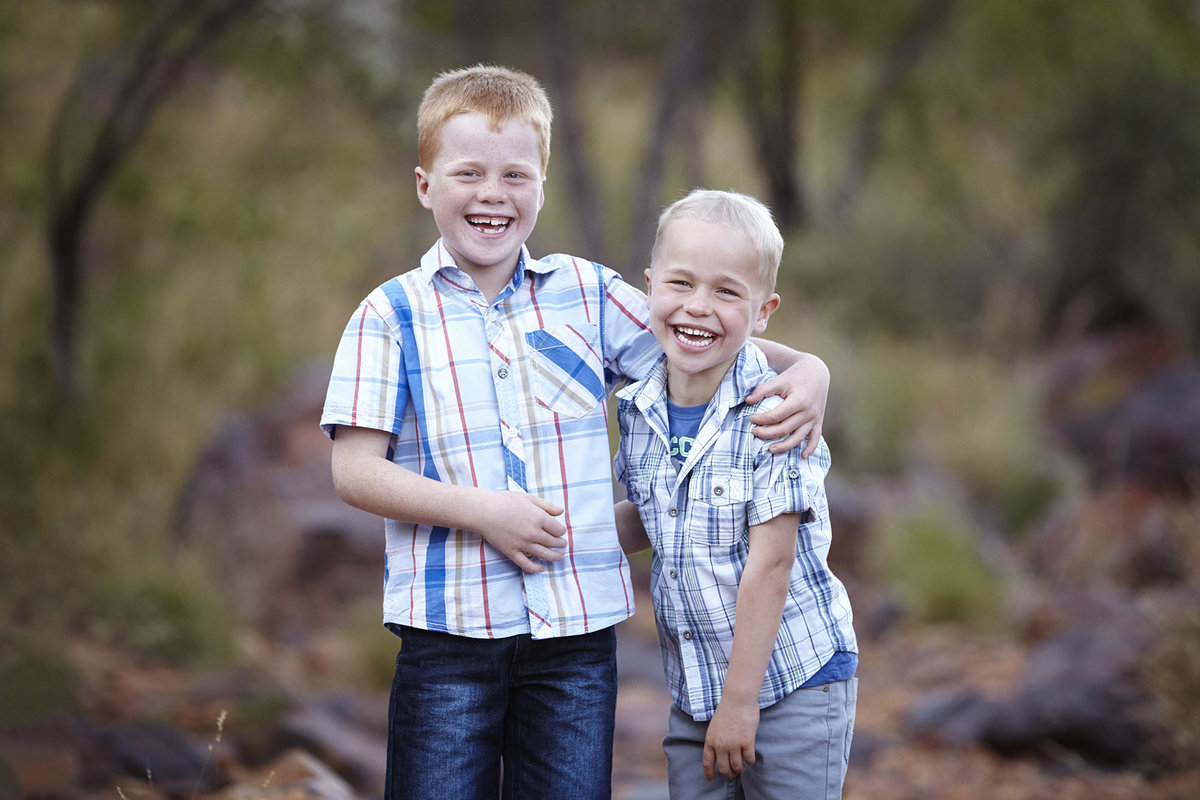 Two boys looking at camera arms around each other laughing