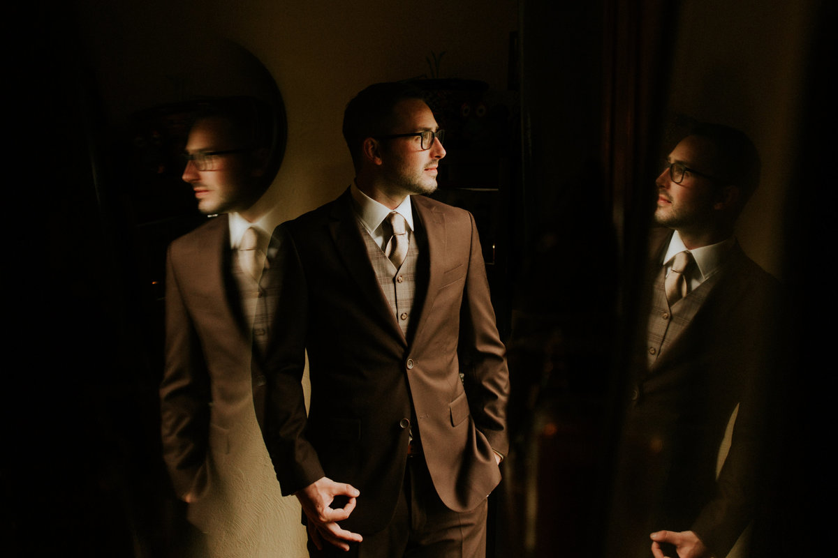 A dapper groom in a brown suit takes a portrait in the moody and dramatic venue