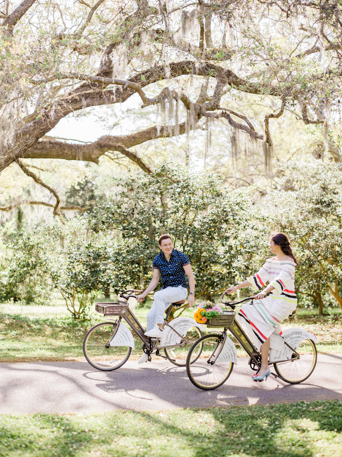 Cute couple riding bikes during engagement pictures at Charles Towne Landing.