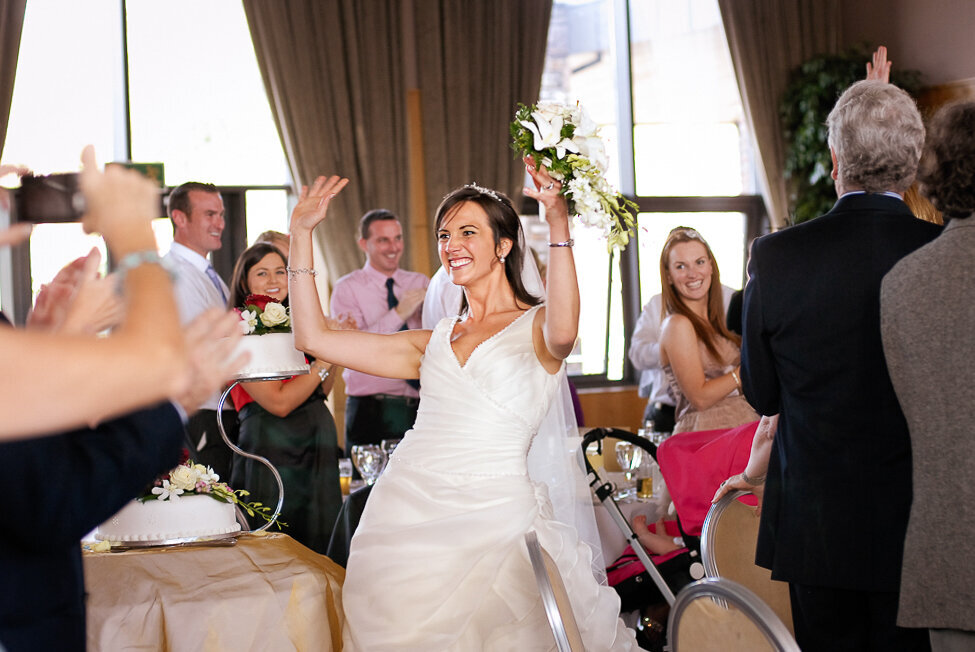 bride wearing a princees style wedding dress with tulle dancing her way into the wedding reception, holding white bouquet in the air while her wedding guests cheer