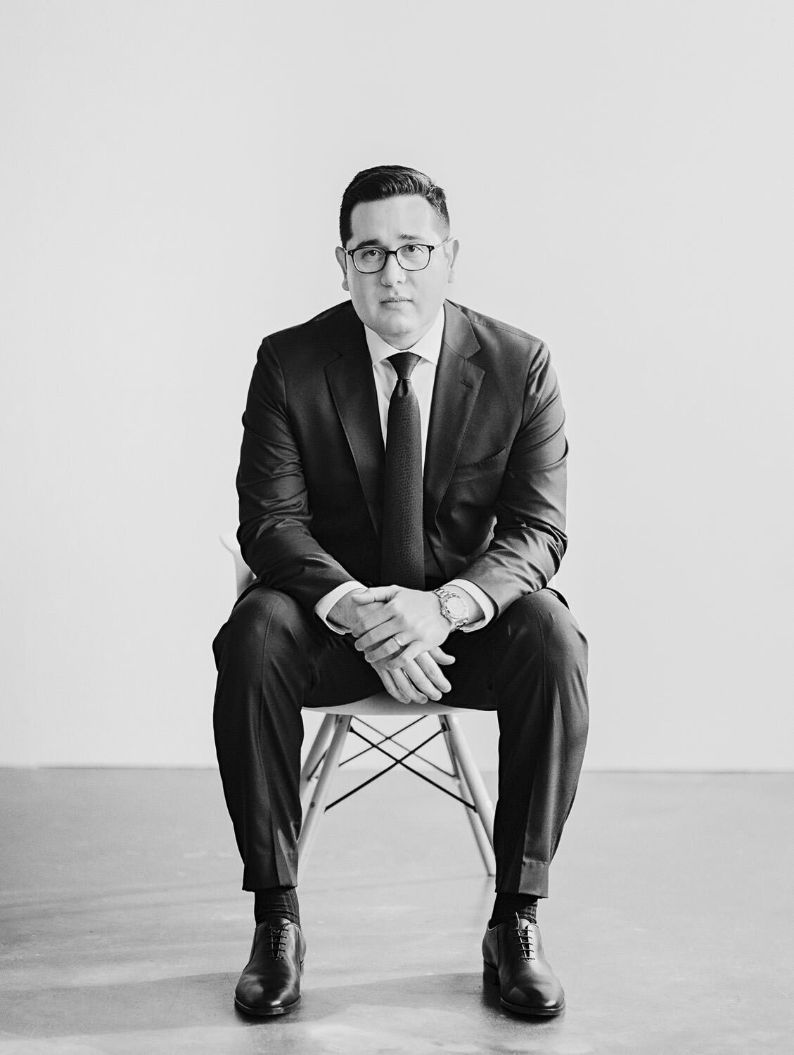 man in glasses and suit sitting in chair black and white