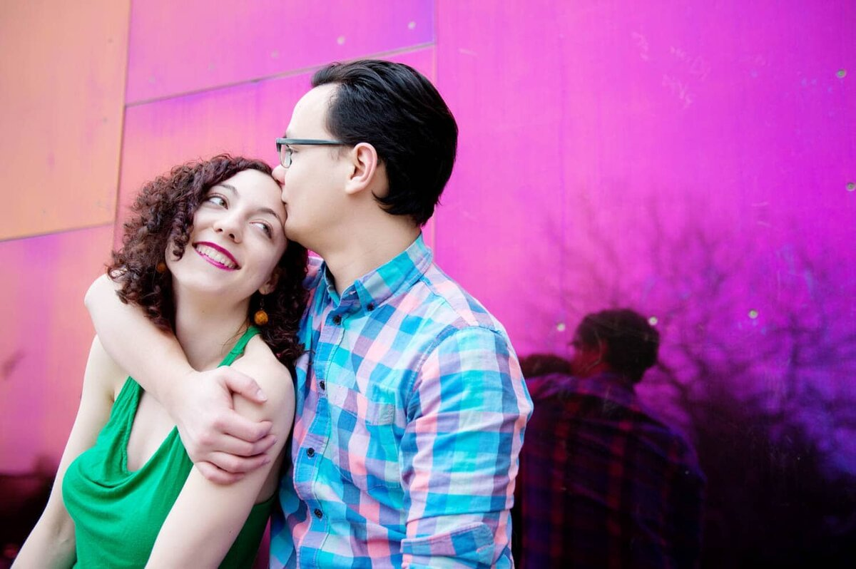 a man kisses a womans head in front of the bright pink wall of the pop museum in seattle