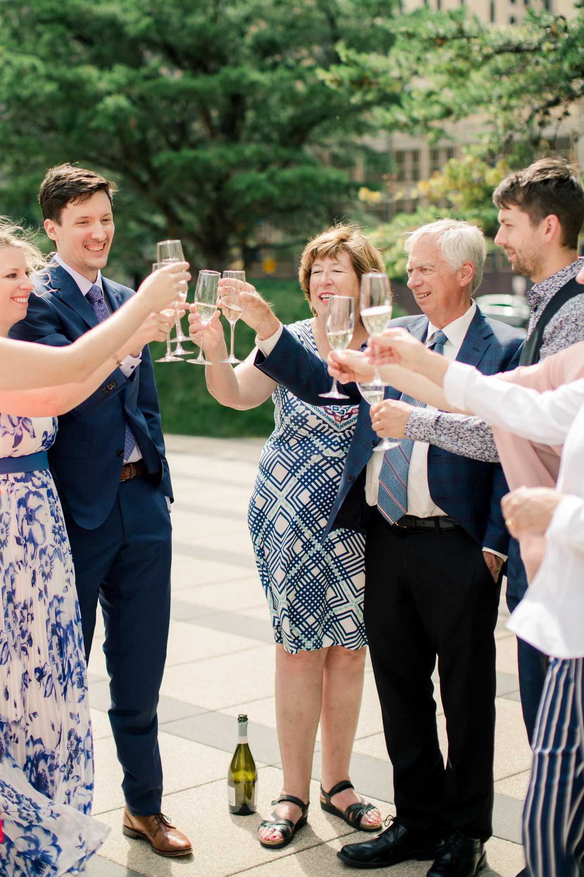 after elopement in downtown minneapolis immediate family cheers with bubbly outside