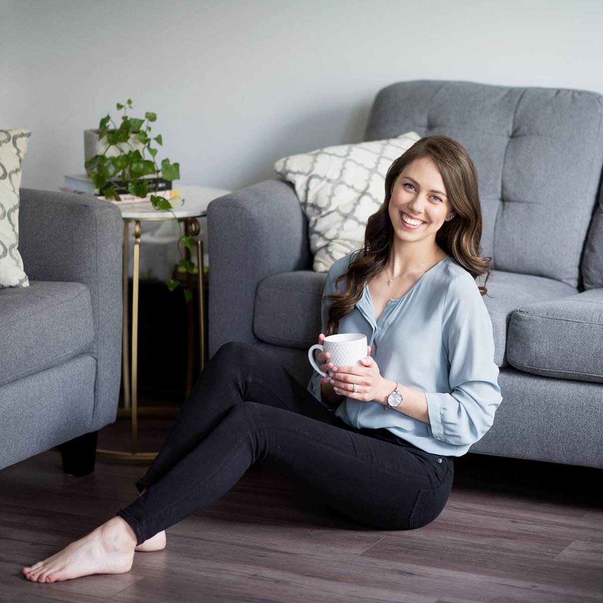 woman sitting on living room floor holding a mug