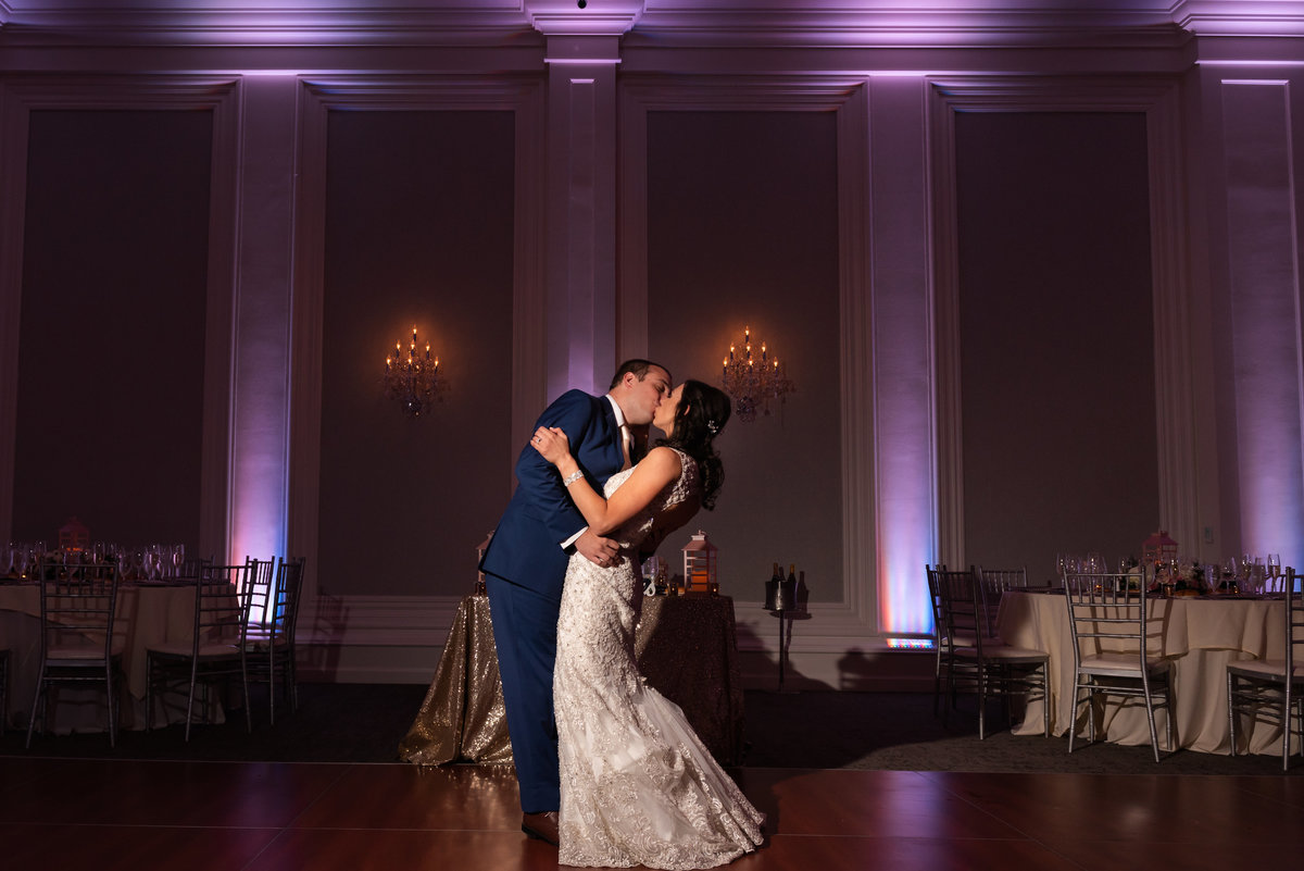 bride and groom kissing in grand ballroom