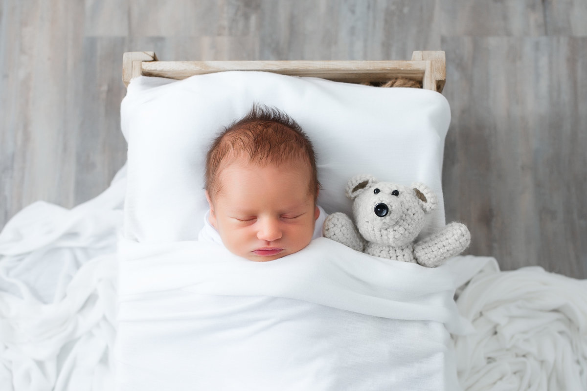 baby boy sleeping in crate with stuffed bear {Milton Newborn Photographer}