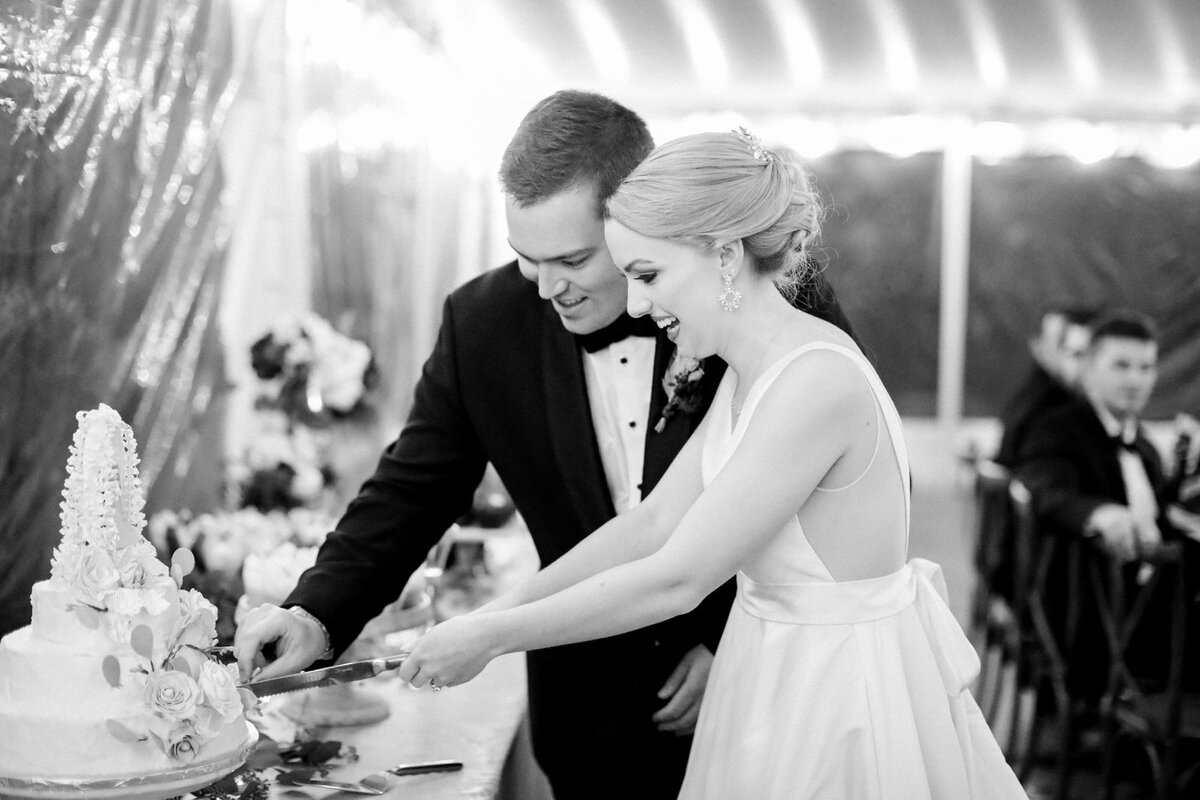 A Greensboro wedding photographer captures a black and white reception photo of a couple at their Summerfield Farms wedding in North Carolina.