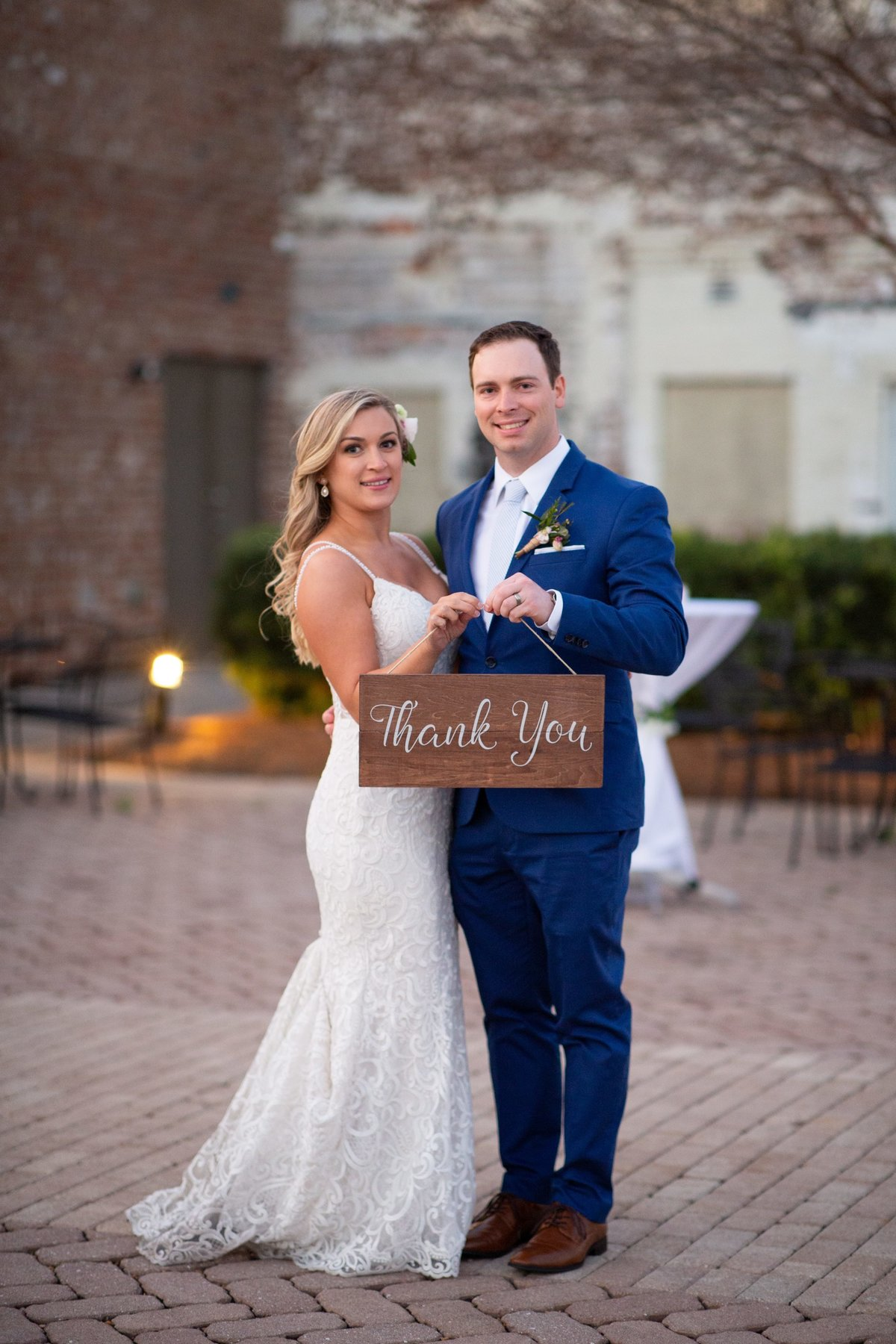 bride and groom holding sign