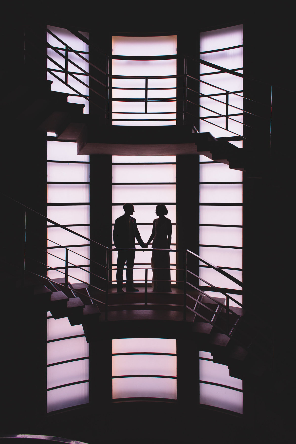 silhouette of bride and groom in front of stained glass window