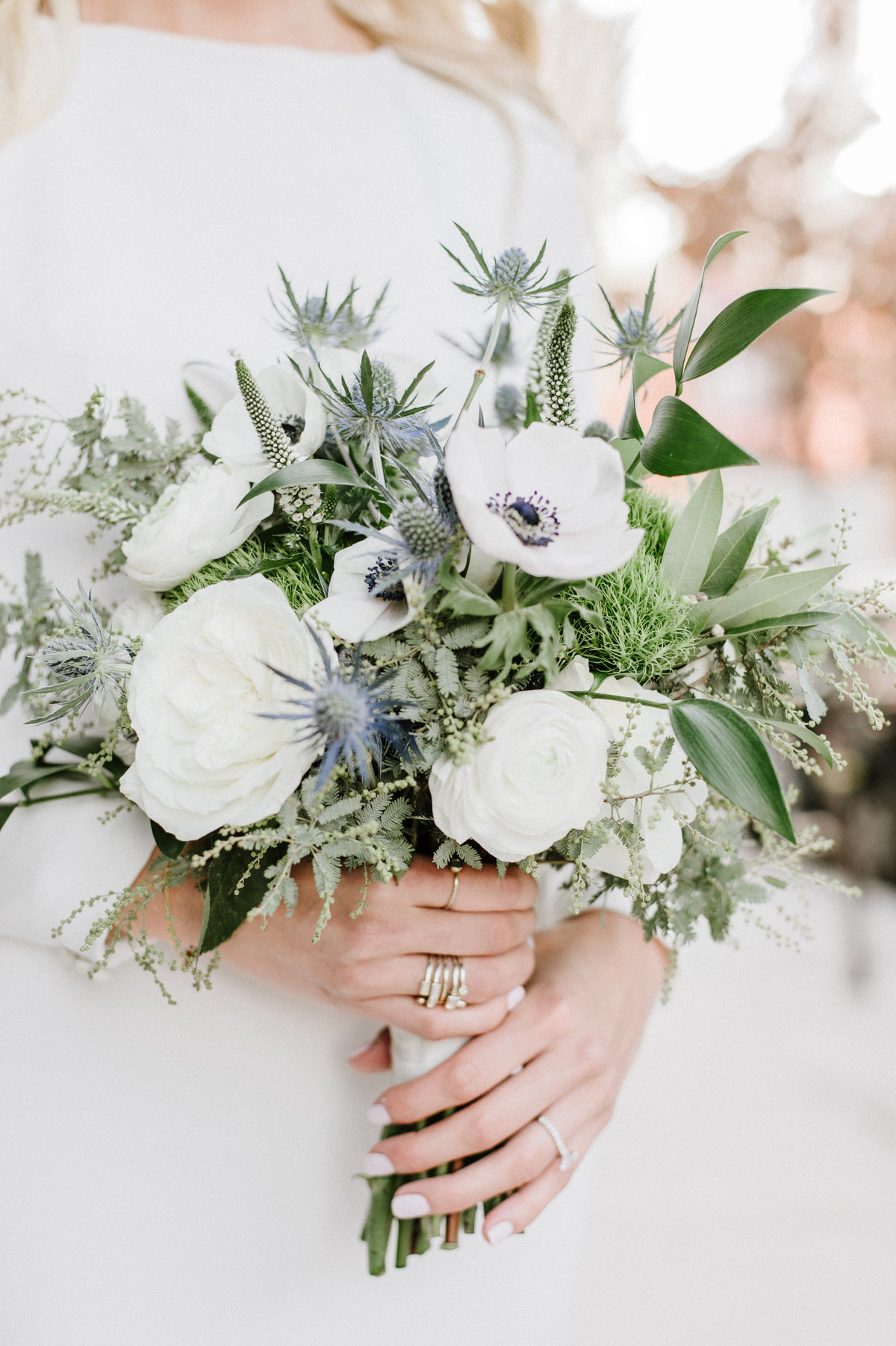 bride holding winter bouquet with blue and white flowers