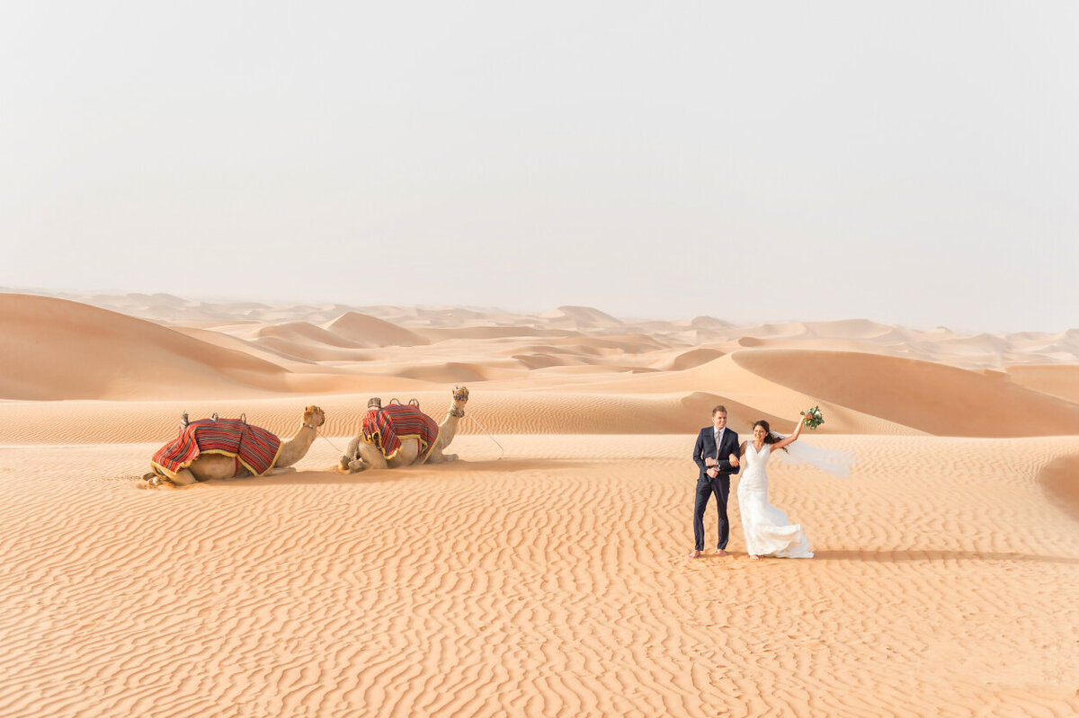 Bride and groom celebrating their wedding amidst the Arabian dunes in Dubai for an elopement photoshoot organized by Lovely & Planned