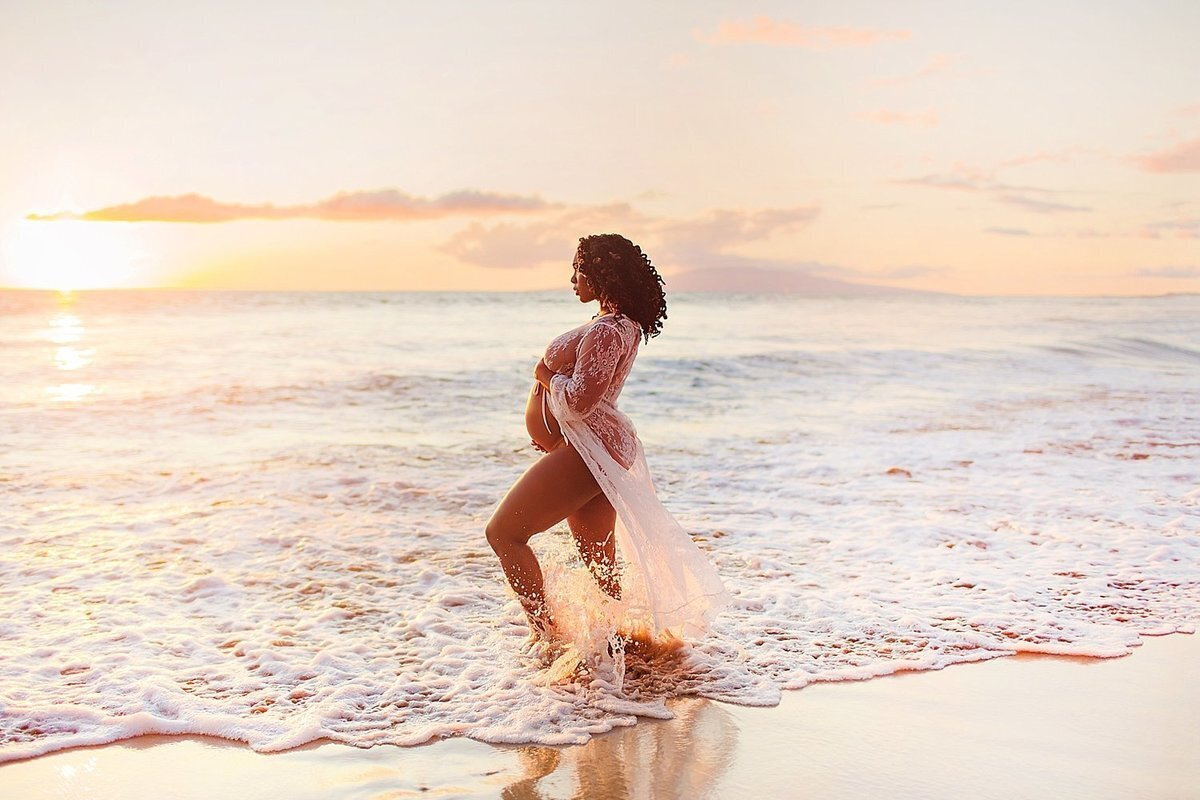 Woman with powerful pose holds her pregnant belly and looks out to sea at sunset