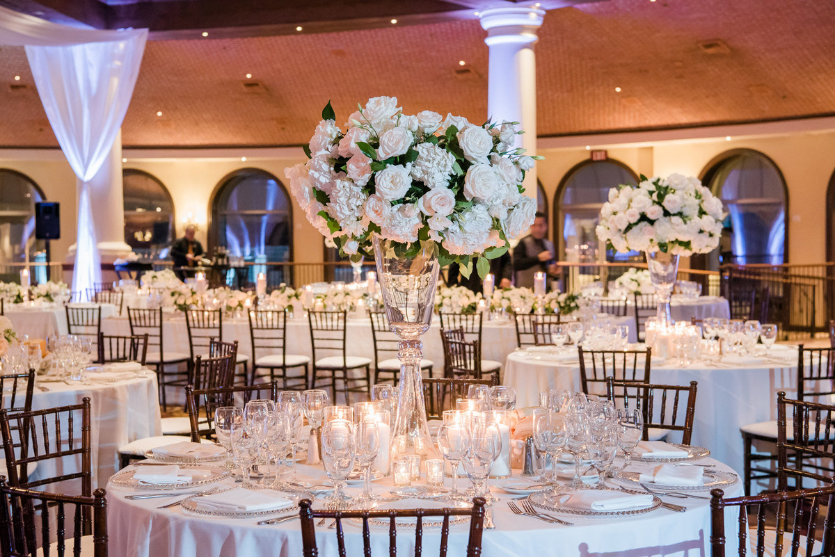a wedding reception photo at JW Marriott Resort and Spa with tall white floral centerpiece with white linen