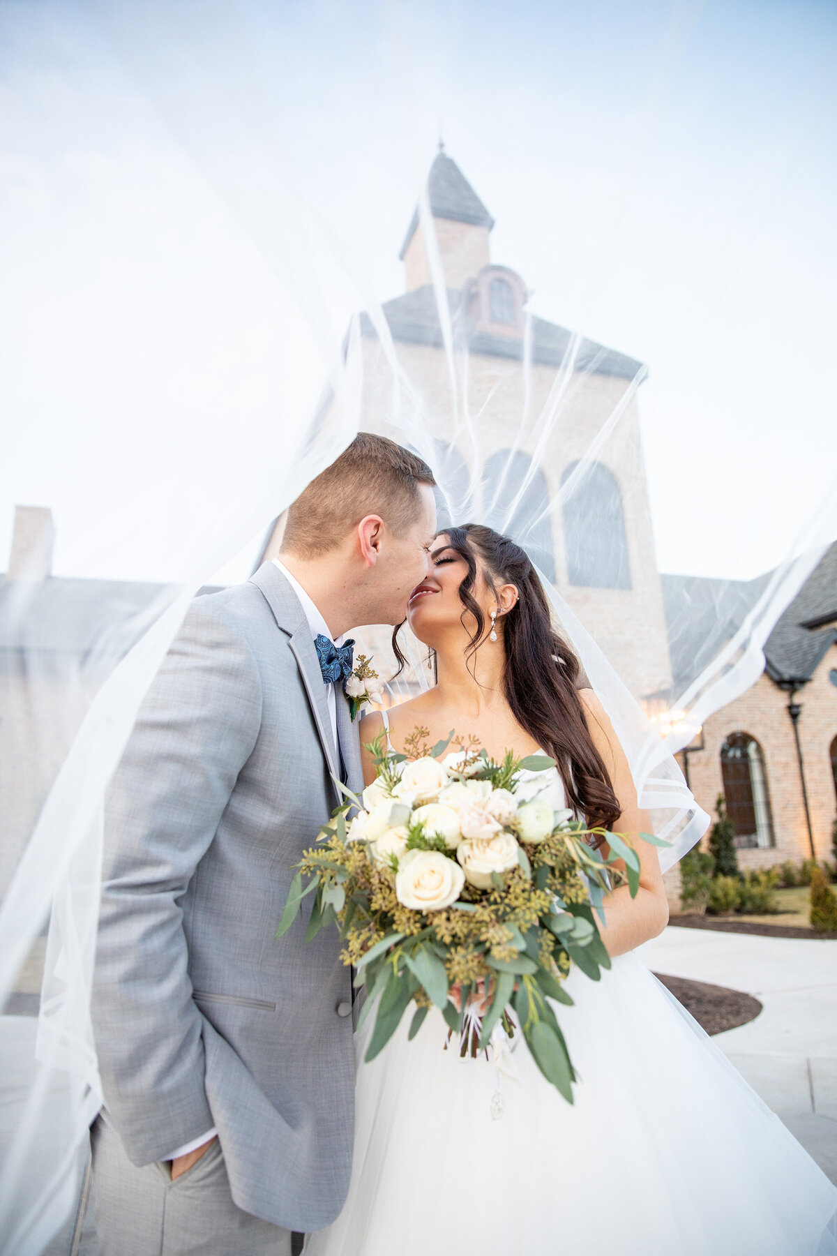 Bride and Groom Kiss Under Her Veil in Front of Iron Manor