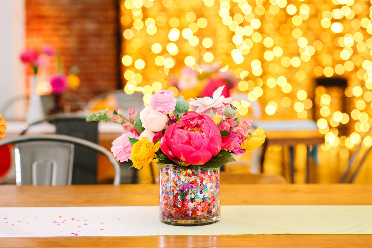 Wedding reception table setting at Unique Space LA with bright colorful floral centerpieces filled with confetti