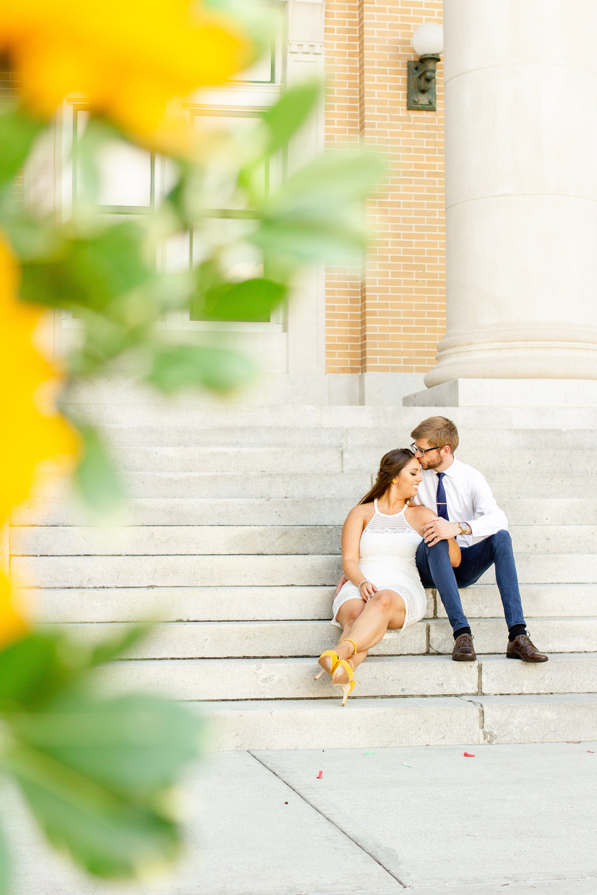 Bride and groom in Clearwater Florida sitting on stairs with sunflower bouquet on their wedding day
