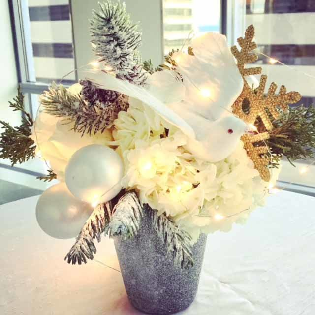 peace on earch flower centerpiece with white dove, white ornaments, flocked evergreen in silver vase