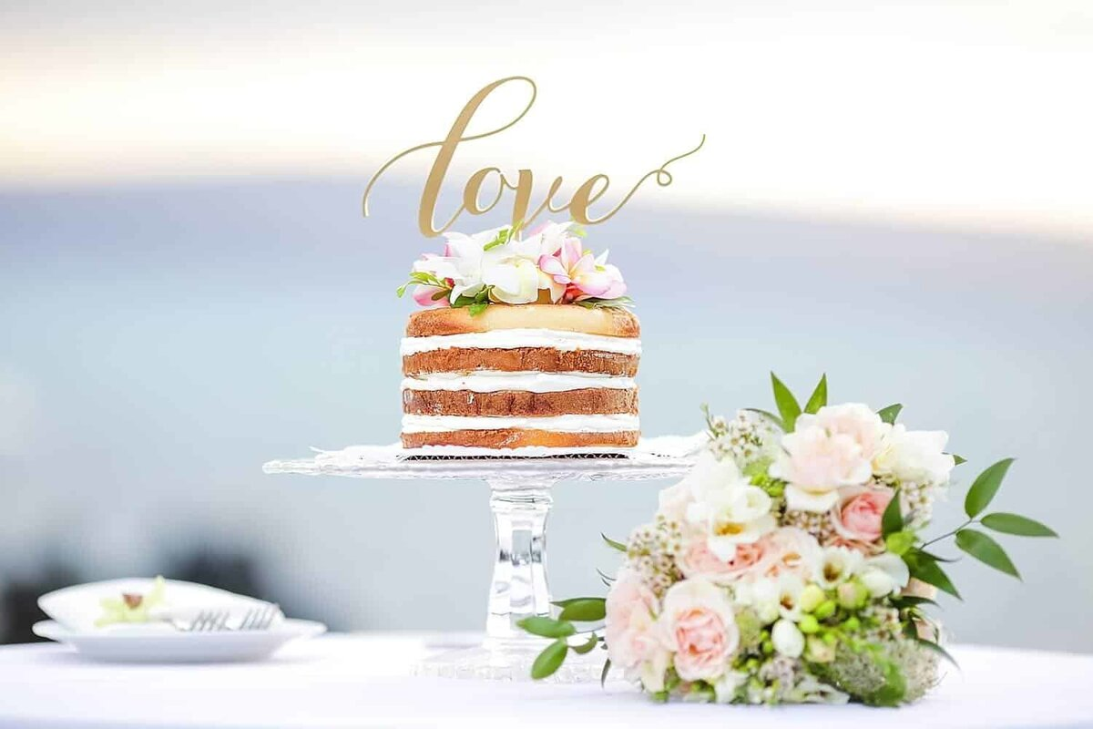 Beautiful simple Maui wedding cake with bouquet in foreground