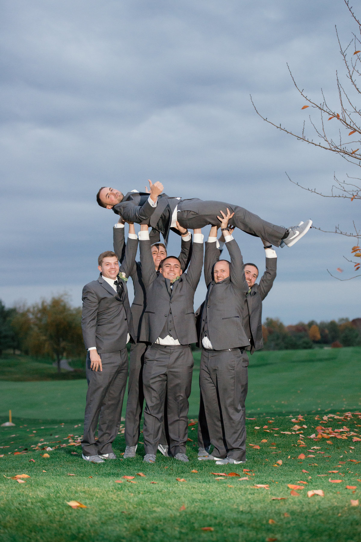 groomsmen holding up the groom on the golf course at Willow Creek Golf and Country Club