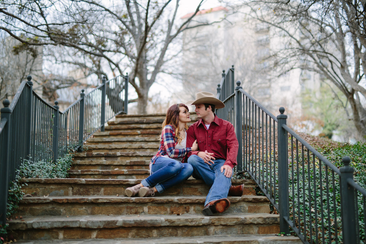 Engagement session by Expose The Heart Photography of an engaged cowboy and cowgirl sitting on the steps of the San Antonio Riverwalk.