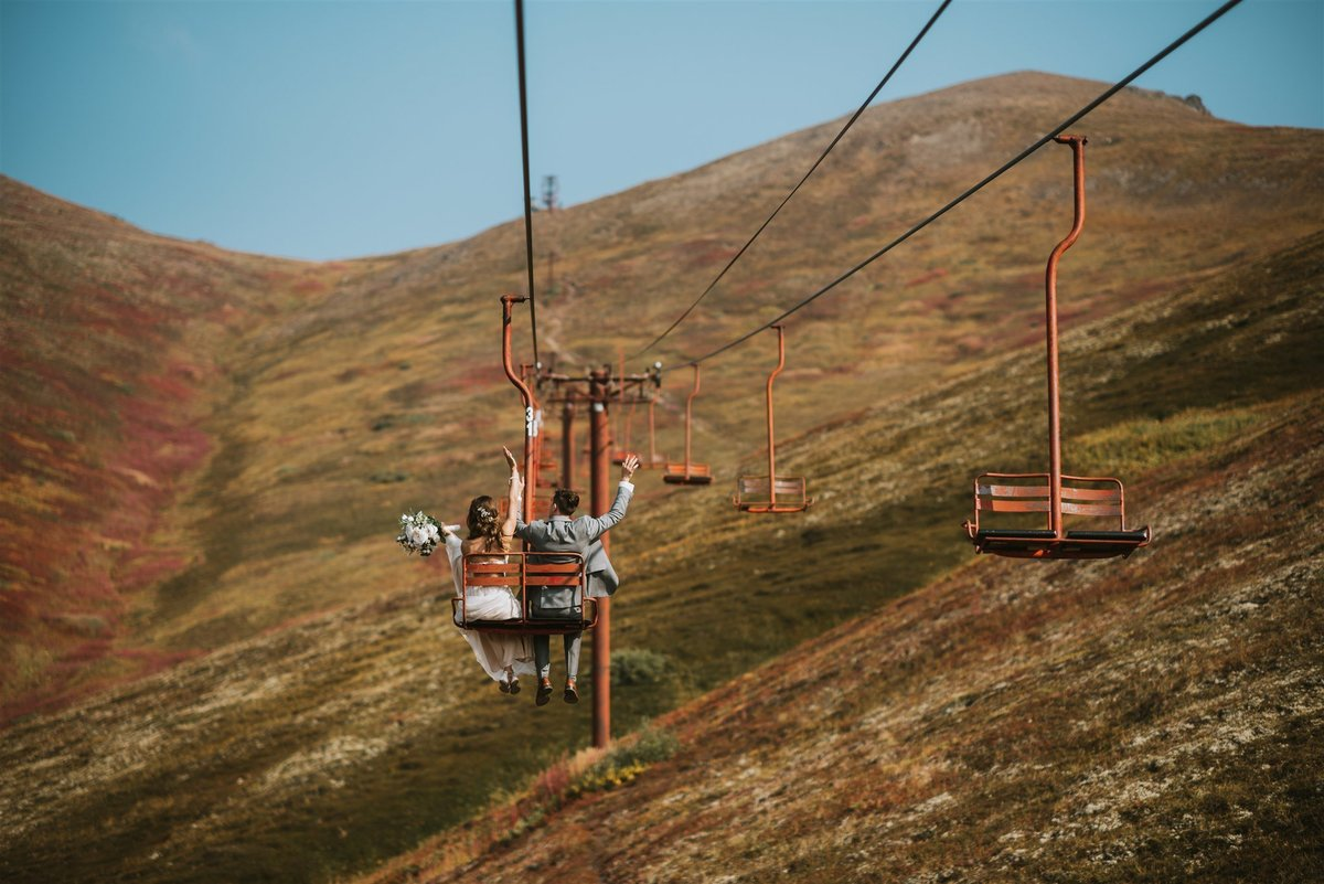 couple cheering about being married on the Arctic Valley Ski lift after their fall wedding with mountain backdrop