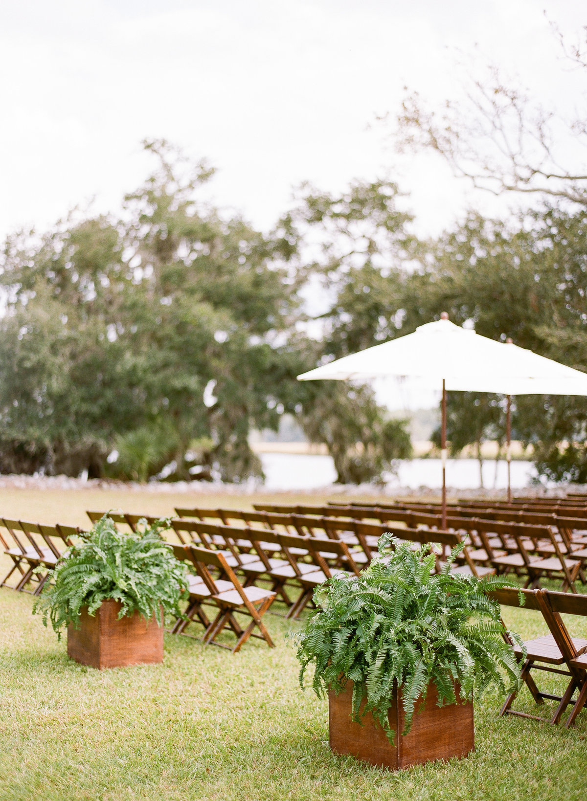 Charleston Wedding Ceremony with Beech Wood Chairs Ferns in Planters and White Umbrellas