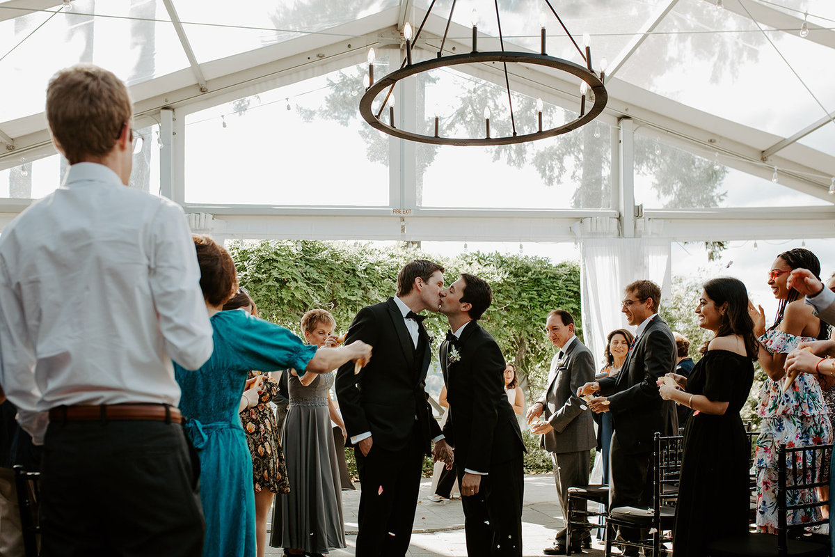 Grooms kissing at the end of the aisle during their wedding ceremony