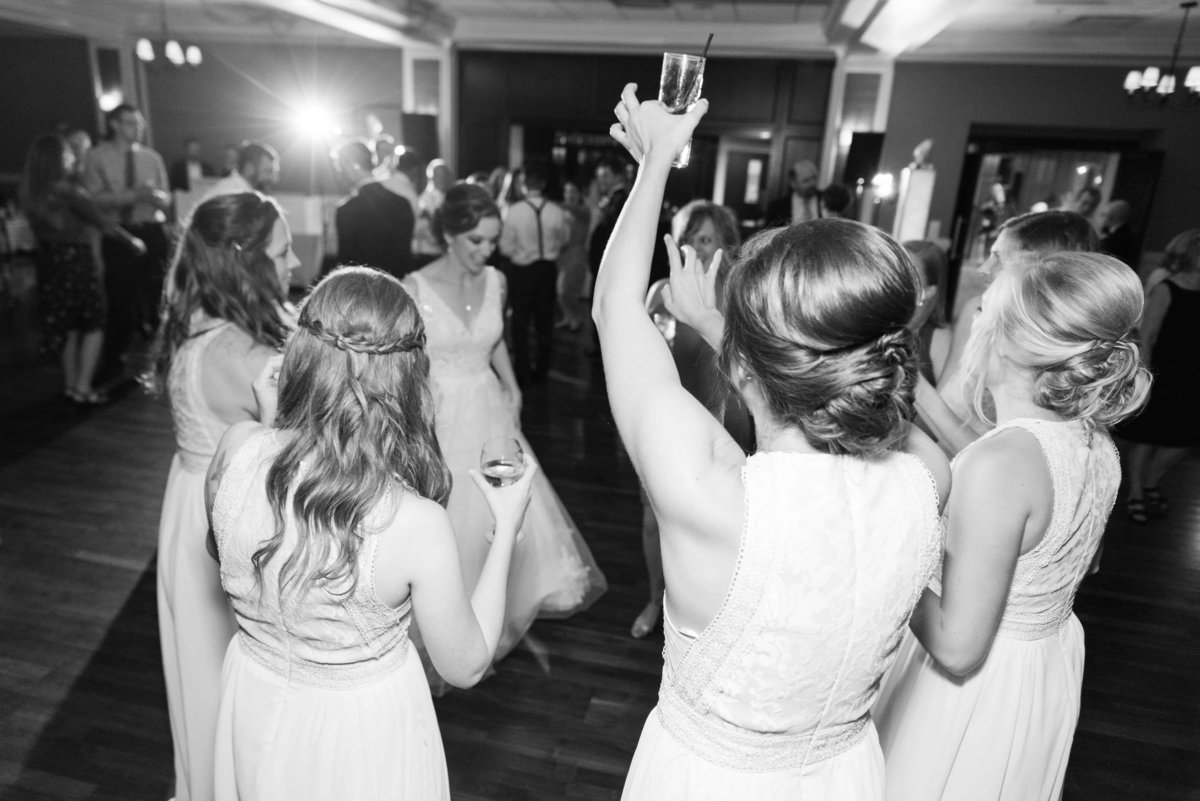 Black and white shot of guest partying during wedding reception.