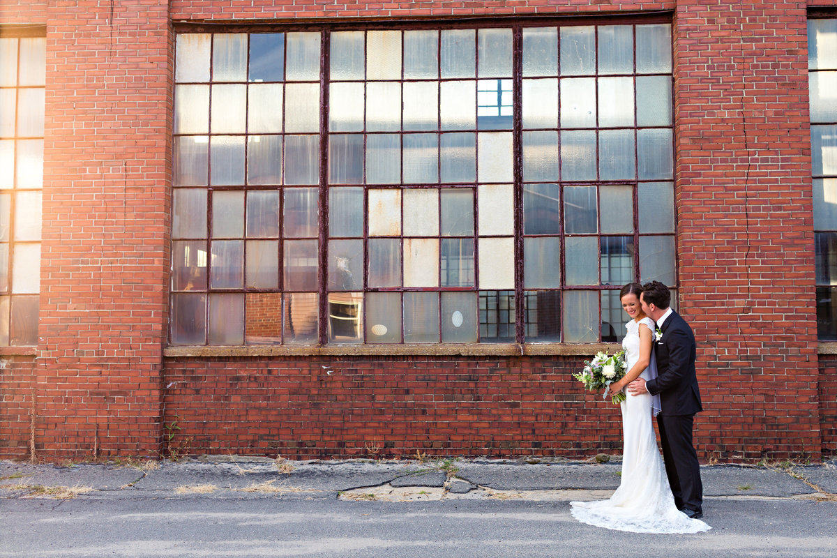 Portland Maine Wedding Photographer the newlyweds laugh and enjoy celebrating their marriage in front of the bricks downtown