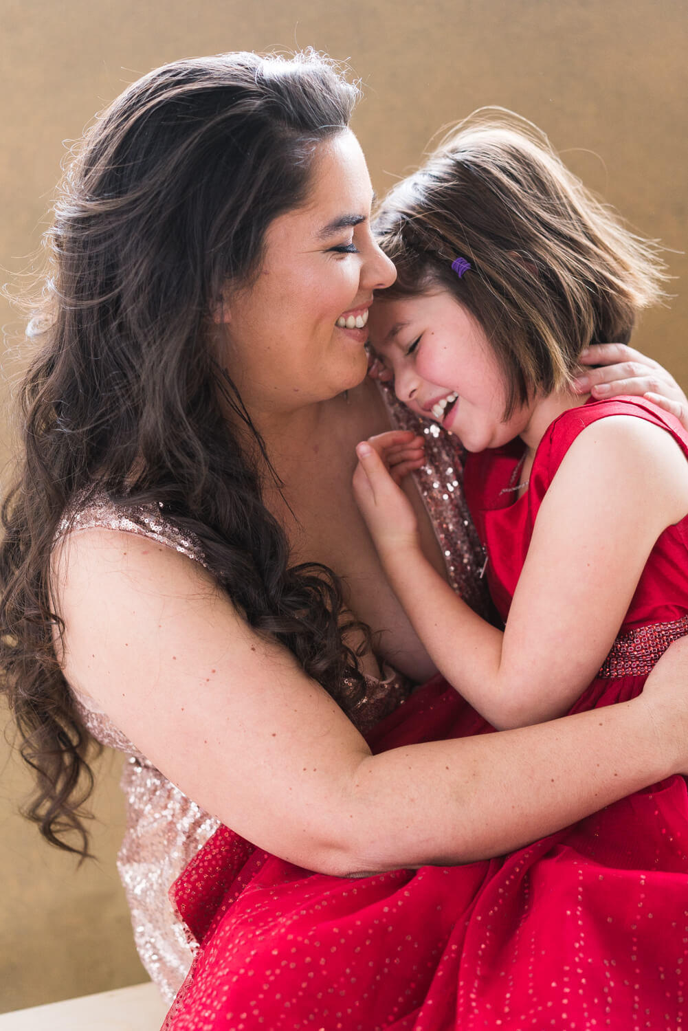 Mother and daughter laughing candidly together in mother daughter photoshoot