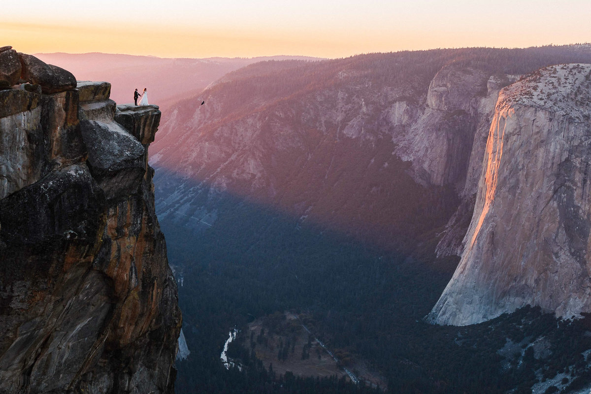 Bride and groom walking on cliff outcrop overlooking Yosemite Valley and El Capitan at purple sunset