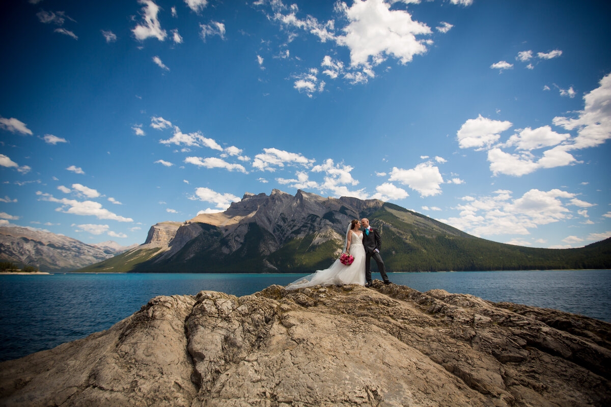 Bride and Groom embrace on their wedding day atop a rocky hill overlooking a beautiful lake.