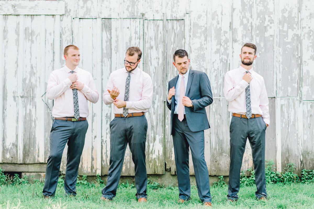 groomsmen in front of white barn