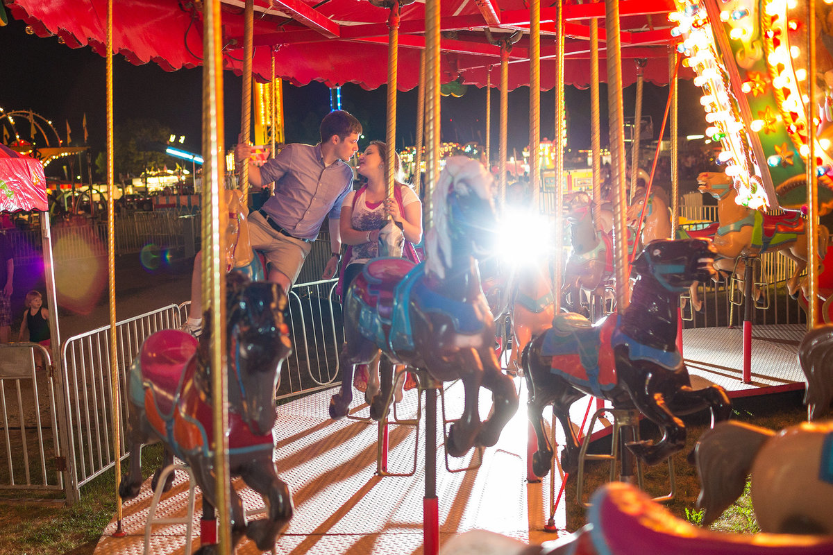 couple riding the merry go round at the county fair during their engagement photography session