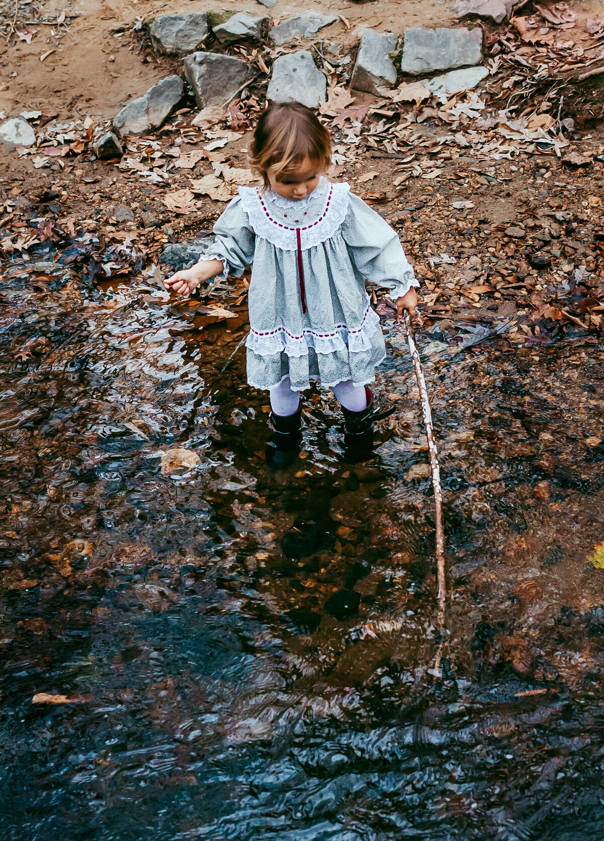Little girl with stick in creek