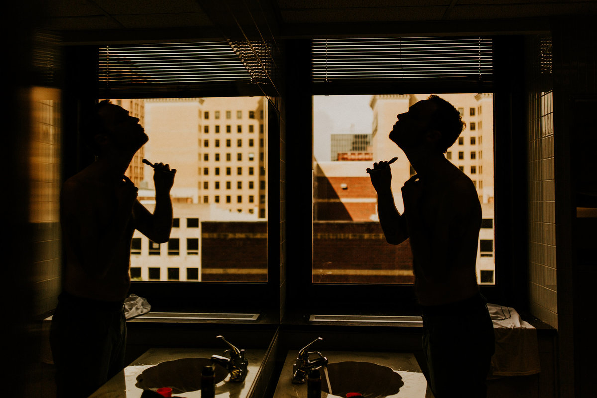 One of the top wedding photos of 2019. Taken by Adore Wedding Photography- Toledo Ohio Wedding Photographers. This is a photo of a groom shaving before the wedding in downtown Toledo Ohio