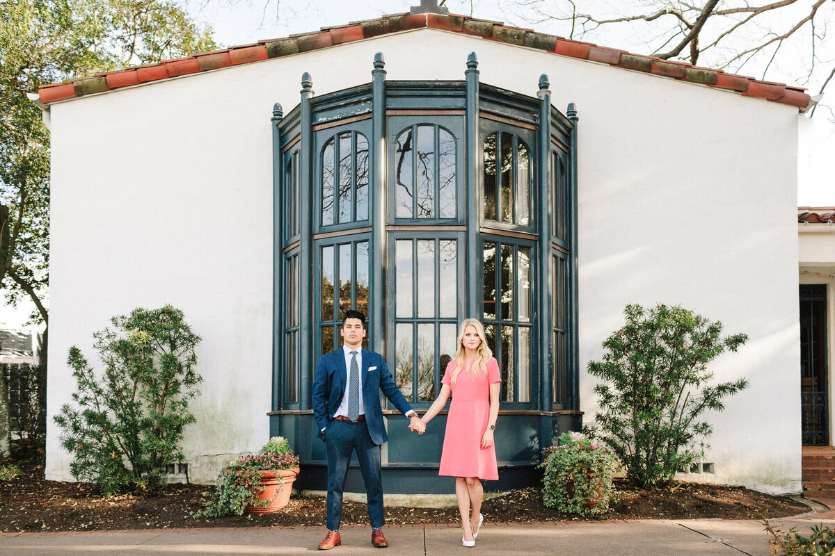 man in blue suite holding hands with woman in pink dress standing in front of Spanish building