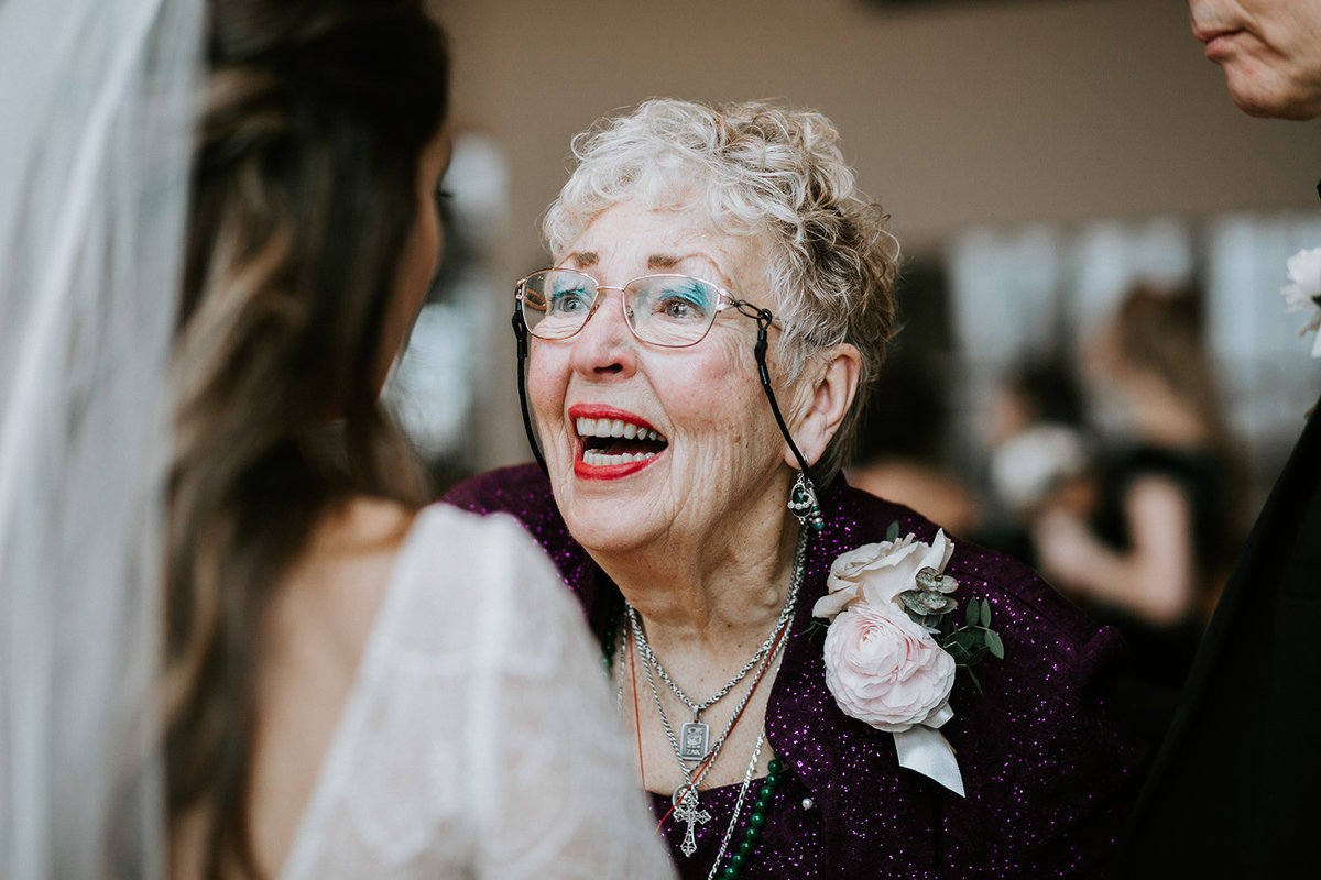 An older lady smiles at a bride.