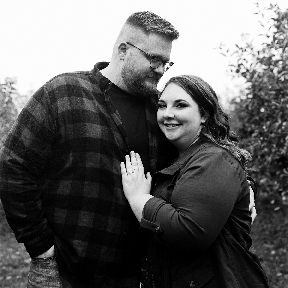 Couple stands for a portrait at apple farm during engagement session