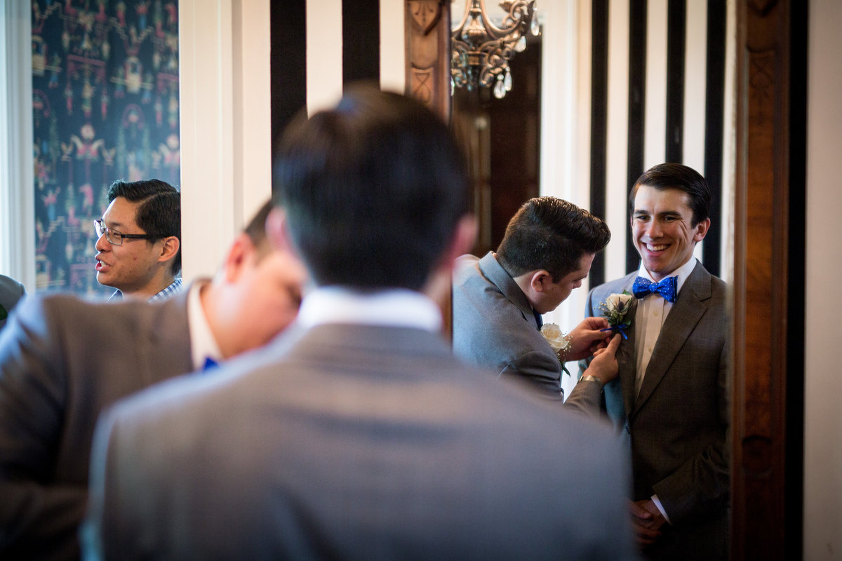 Groomsmen assist groom with tie as he gets ready for wedding ceremony at Grace Point Church