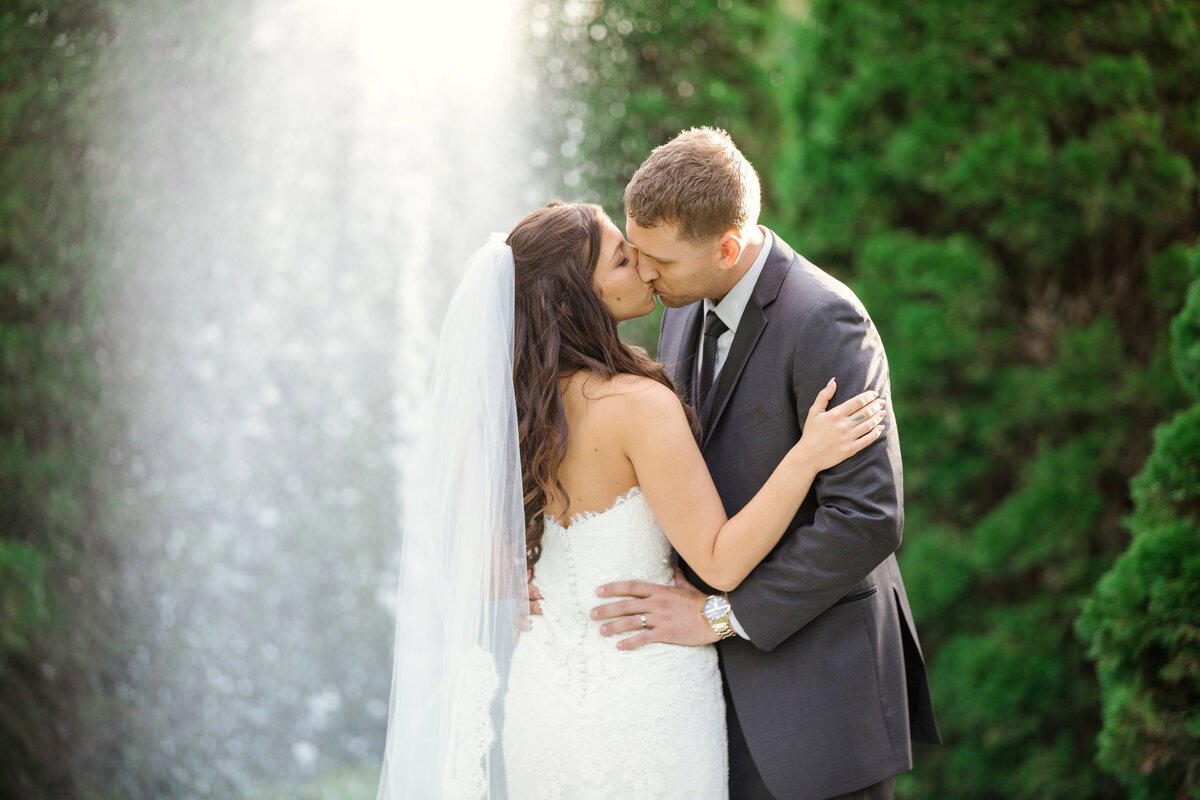 bride and groom kissing wedding photo under fountain at The Carltun