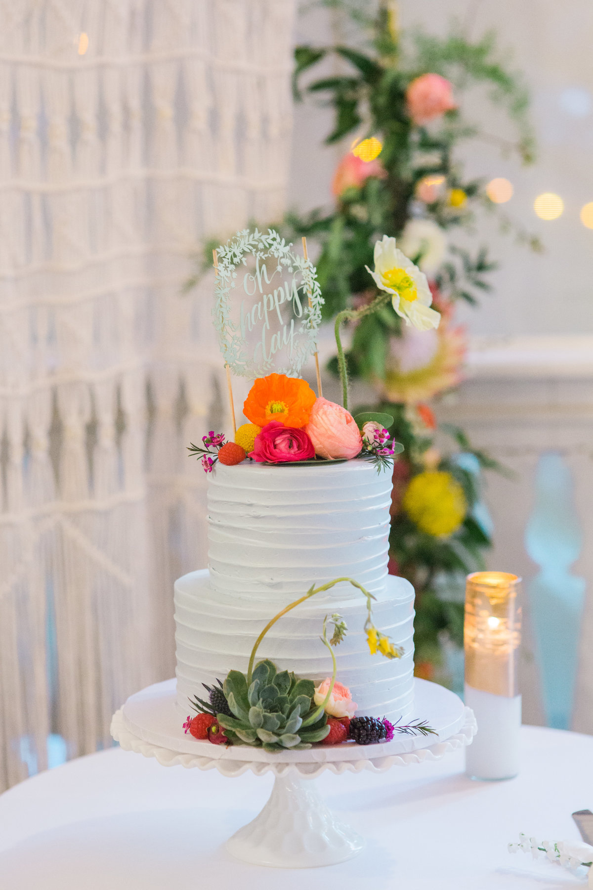 Full wedding cake from Moustache Baked Goods in front of boho marame wall screen at Madrona Manor in Healdsburg California