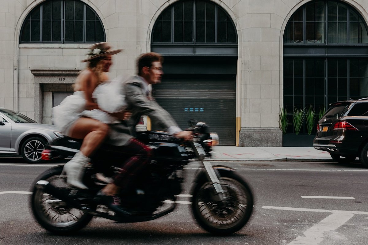 Blurred photo of Hayley Paige and Conrad Louis on a motorcycle in NYC