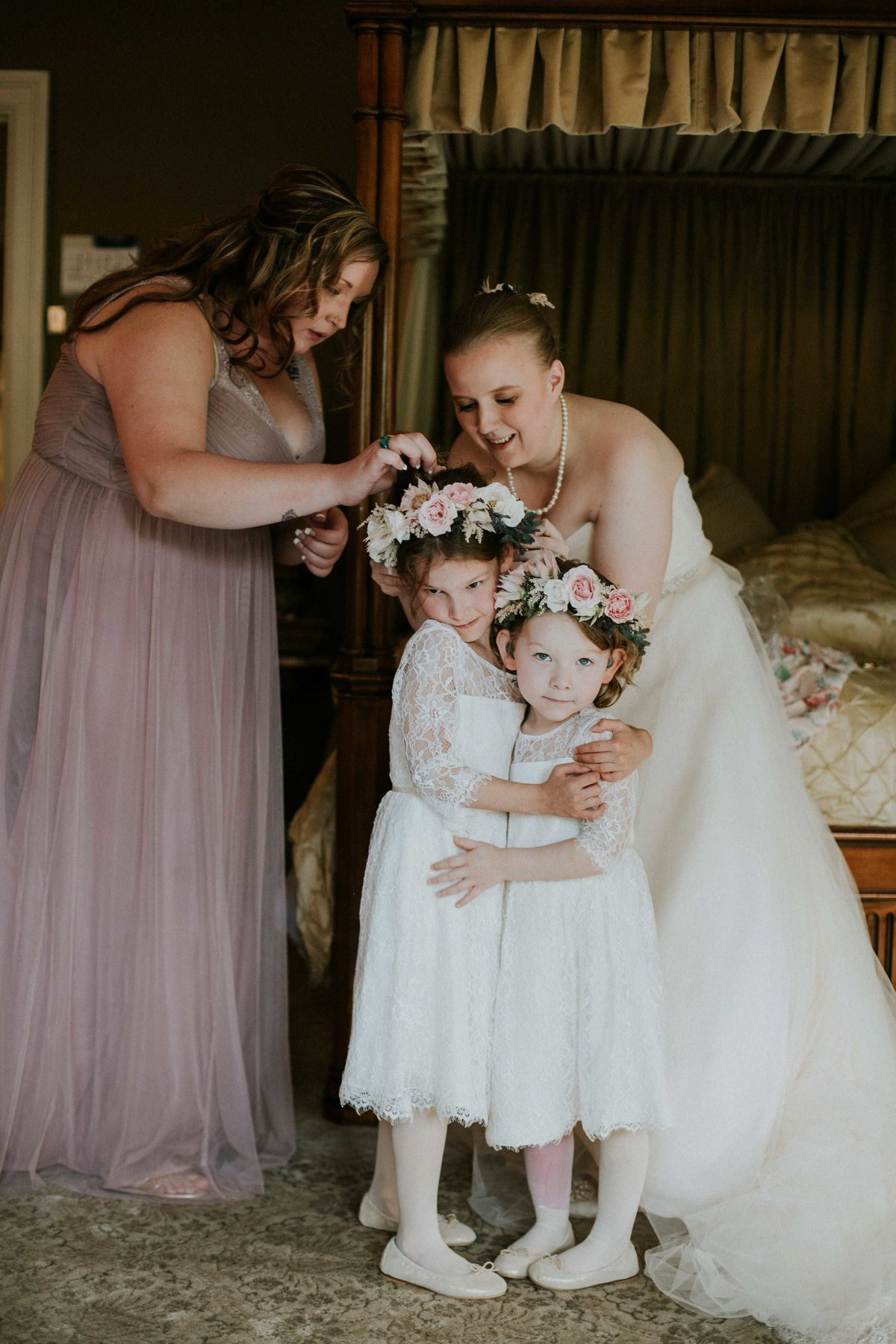 Flower girls hug while bride secures flower crown at Laurel Hall Wedding