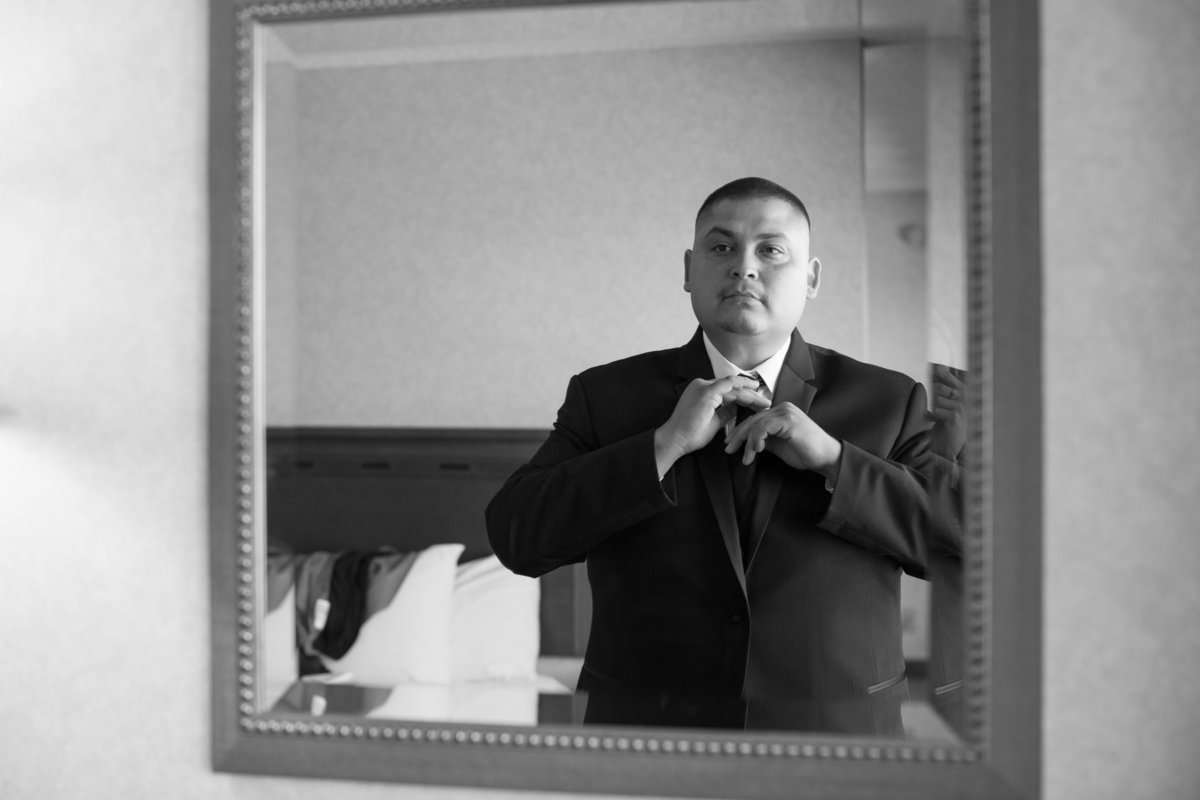 groom preps suit and tie before wedding at hotel in los angeles california
