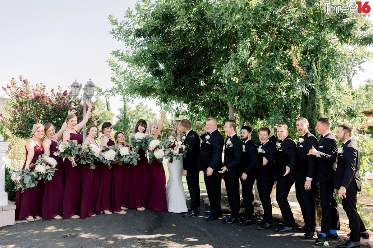 Bridal party cheering as Bride and Groom kiss
