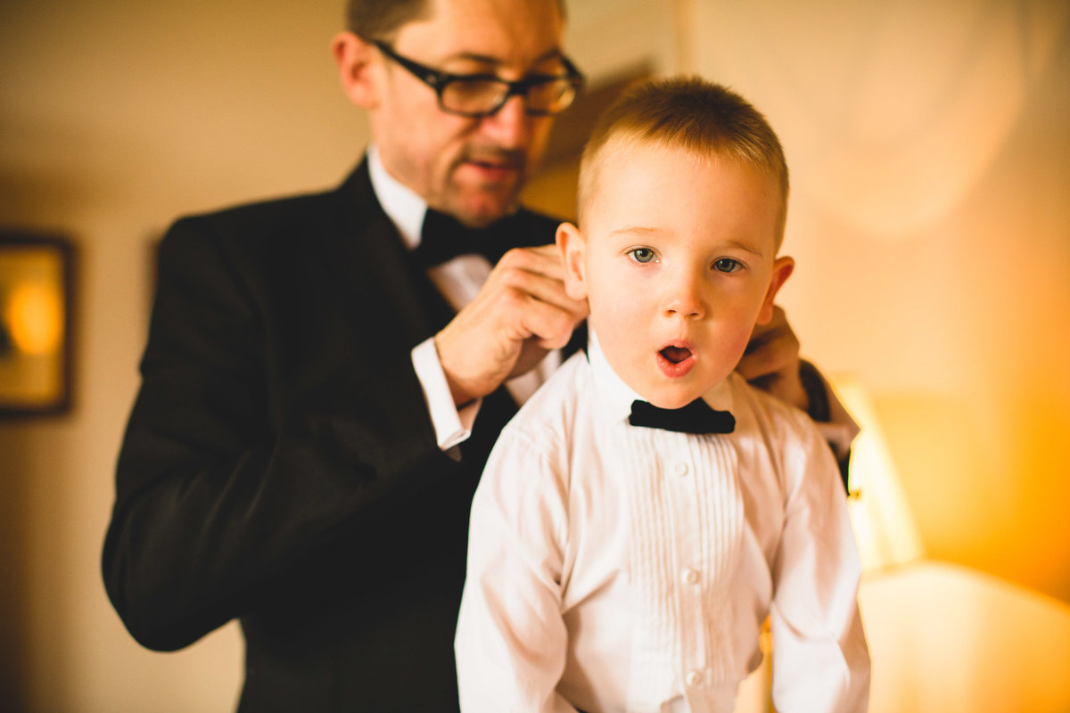 dad dresses boy in tuxedo and bow tie for wedding at thornton manor